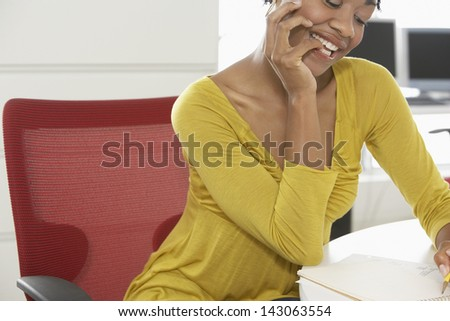 Happy African American woman writing on notepad at office desk - stock photo