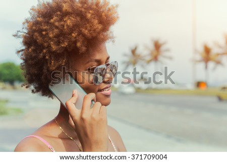 Happy african american young woman in sunglasses calling on smartphone, ocean beach in the background - stock photo