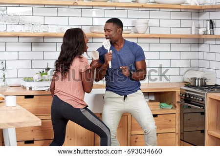 Happy african black couple having fun dancing in modern kitchen