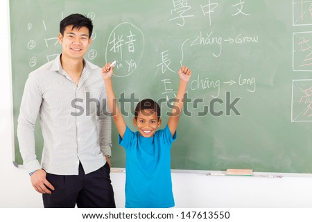 happy african boy with hands up after writing answer on chalkboard - stock photo