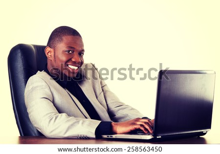 Happy african businessman with a laptop in the office.
