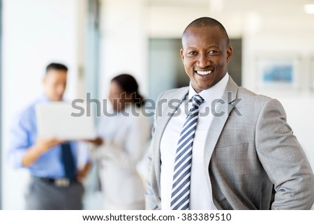happy african corporate worker in office with colleagues on background