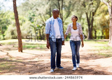 happy african couple enjoying a walk at the park - stock photo