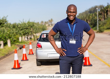 happy african driving instructor standing in testing ground - stock photo