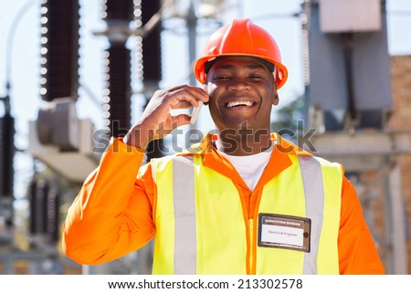happy african electrician using cell phone in electric substation - stock photo