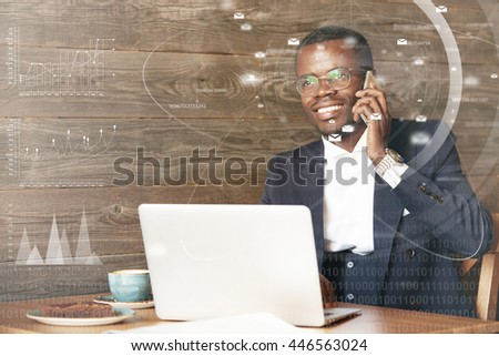 Happy African entrepreneur in glasses smiling showing his white teeth, talking on the phone with his family while working at a cafe using laptop computer. Double exposure with graphics and diagrams