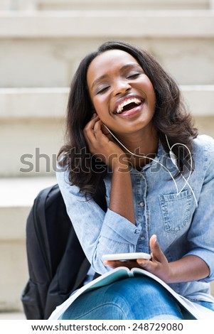 happy african female university student listening to music on campus - stock photo
