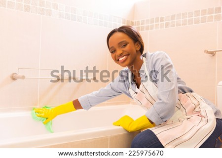 happy african girl cleaning up bathtub at home