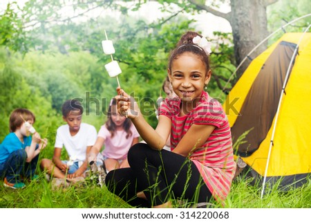 Happy African girl holding stick with marshmallow  - stock photo