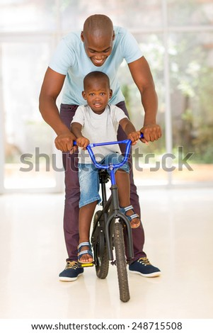 happy african man helping his son to ride a bike indoors - stock photo