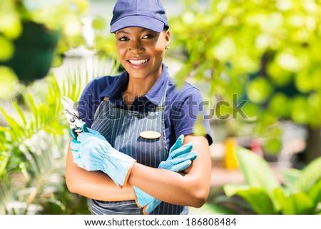 happy african nursery worker holding garden tool - stock photo