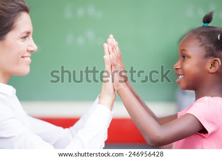 Happy african schoolgirl and female teacher doing high five after math lesson. - stock photo