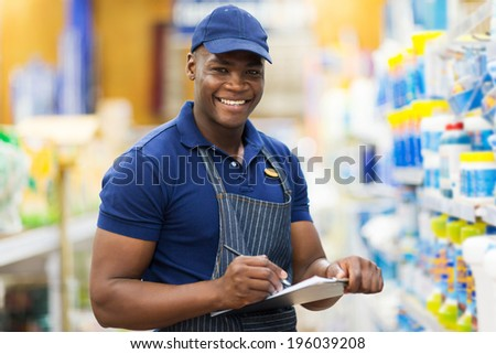 happy african shop assistant checking stock in supermarket - stock photo