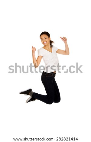 Happy african teen woman jumping with thumbs up. - stock photo
