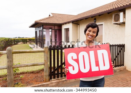happy african woman holding sold sign in front of house - stock photo