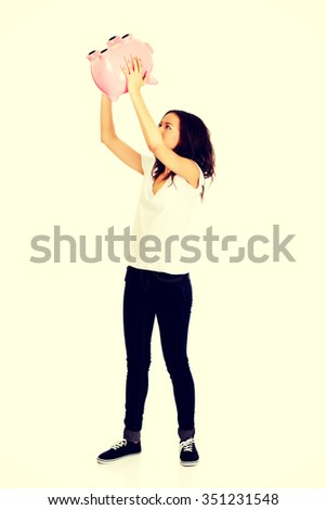 Happy african woman shaking piggybank. - stock photo