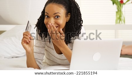 Happy African woman smiling with laptop and credit card - stock photo