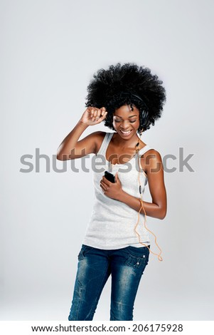 Happy african woman with afro and casual clothing dancing to the music she is listening to from her phone - stock photo