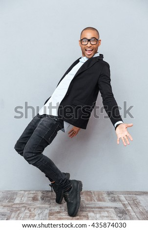 Happy african young man in glasses dancing and smiling - stock photo