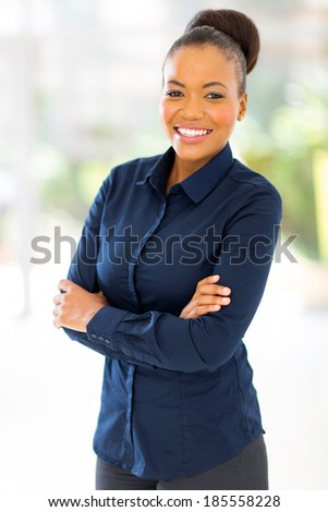 happy afro american businesswoman with arms crossed in office