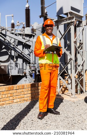 happy afro american electrical engineer with clipboard in power plant - stock photo