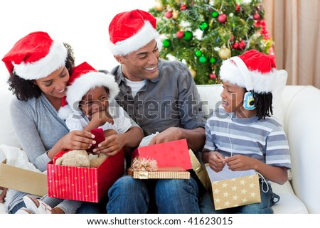 Happy Afro-American family opening Christmas presents at home - stock photo