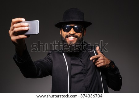 Happy afro american man in fashion cloth making selfie photo on smartphone over black background - stock photo