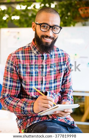 Happy afro american man sitting on the table with notepad and pencil in office and looking at camera - stock photo