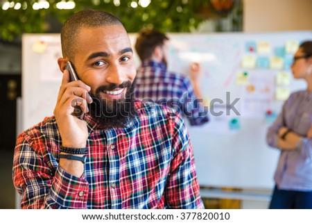 Happy afro american man talking on the phone in office with colleagues on background - stock photo