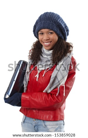 Happy afro-american woman holding laptop computer, dressed for winter. - stock photo