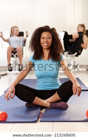 Happy afro girl sitting in tailor seat at the gym, relaxing, smiling. - stock photo