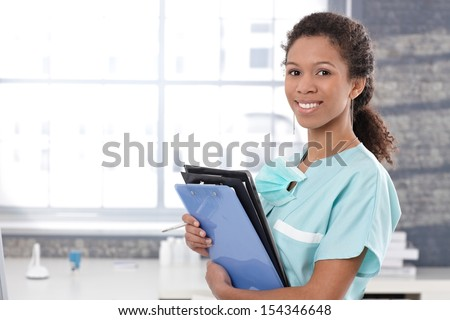 Happy afro medical worker holding case sheets, smiling. - stock photo