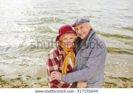 Happy aged couple by seaside looking at camera - stock photo