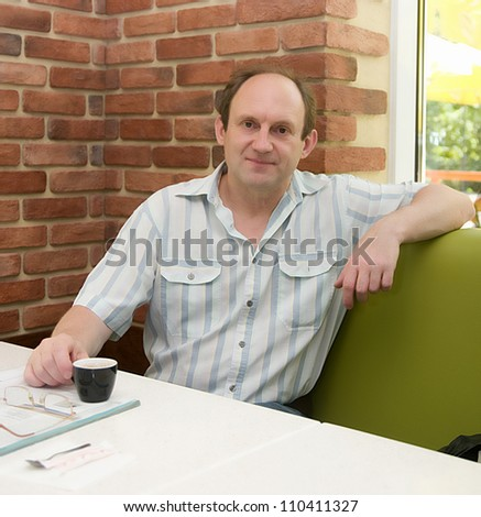 Happy aged man with coffee in cafe