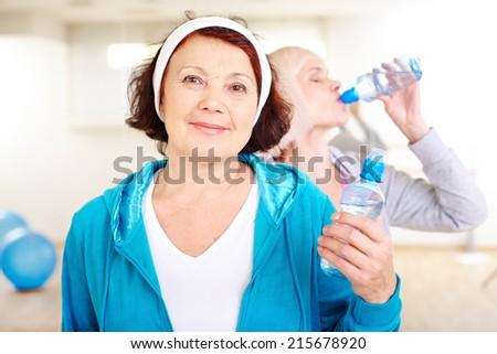 Happy aged woman with plastic bottle of water on background of other female drinking - stock photo
