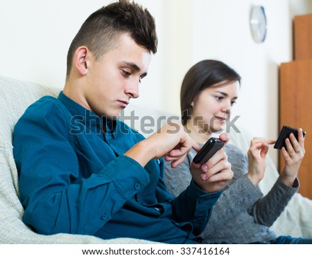 happy american brunette and teenager looking at screens of smartphones..focus on boy