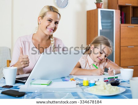 happy American businesswoman browsing internet at home, daughter drawing  in pencil. focus on woman - stock photo