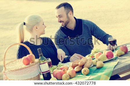 happy american couple having picnic in sunny spring day at countryside - stock photo