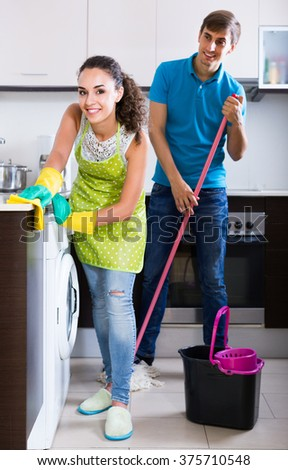 Happy american family couple cleaning in the kitchen together and smiling. focus on woman