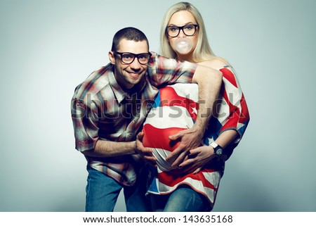 Happy american family (pregnancy) concept: portrait of two funny hipsters (husband and wife) in trendy glasses and clothes playing with their bubble gum. Copy-space. Studio shot - stock photo