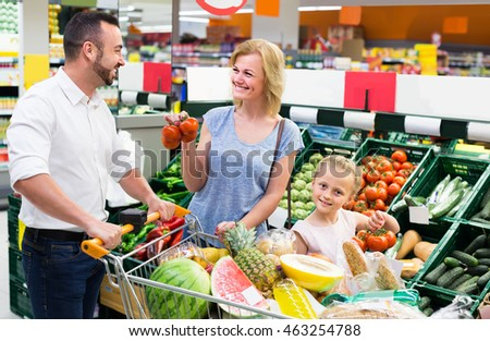 happy american family shopping various fresh vegetables in supermarket