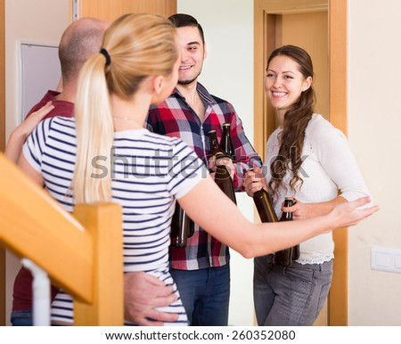 Happy american  guests with bottles standing in doorway and smiling - stock photo