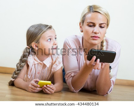 Happy american mother and small girl playing with mobile phones indoor - stock photo
