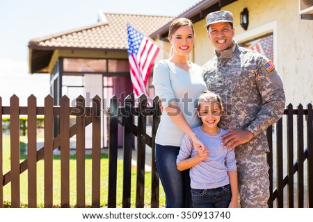 happy american soldier reunited with family outside their home - stock photo