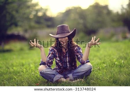 Happy American woman in a cowboy hat field wild flowers - stock photo