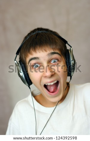 Happy and Amazed Teenager in Headphones Listening to the Music