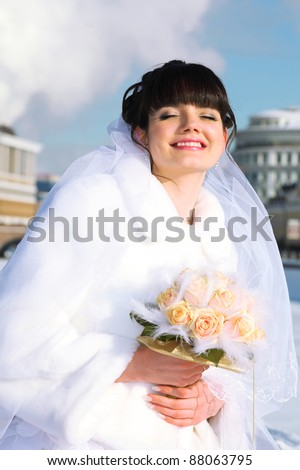 happy and beautiful bride smiles and holds bouquet of roses at winter outdoors - stock photo