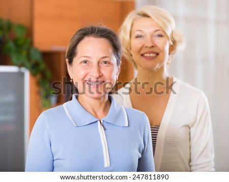 happy and beautiful senior women posing at home interior - stock photo