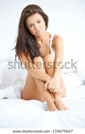 Happy and Beautiful woman sitting on white bed