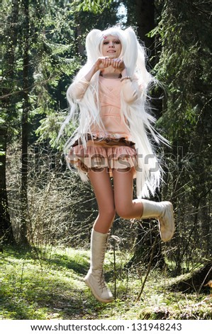 Happy and beautiful young girl jumping high in a forest